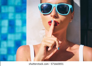 Keep secret! Gossip girl. Pretty young woman showing silence sign with her finger on lips at swimming pool.