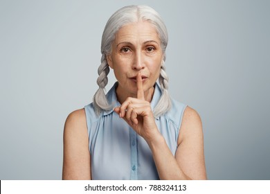 Keep secret, please. Elderly woman with two grey plaits holds finger on lips, shows silence sign, asks to be mute and not tell confidential information to everybody, isolated over blue background