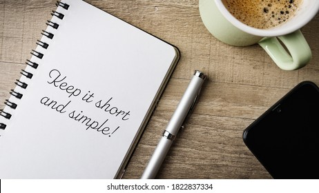 Keep it short and simple!. Flat lay. Work area with notepad, pen, cell phone and a cup of coffee.