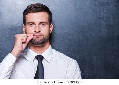 Keep silence! Handsome young man in formalwear showing a sign of closing mouth and looking at camera while standing against blackboard