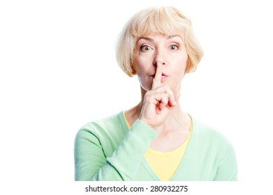 Keep silence! Serious middle aged woman holding finger on mouth and looking at camera while standing isolated on white background