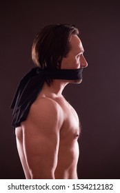 Keep silent. Profile of topless mature man standing with black band covering his mouth while looking straight and expressing sadness