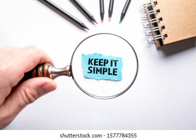 Keep it simple. Colored pencils on a white background. Man's hand, holding magnifying glass