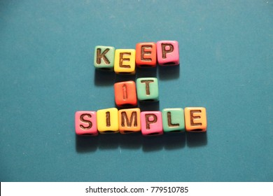 Keep it simple slogan words and letters spelled with colorful alphabet bead blocks.