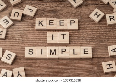 Keep it simple slogan written with cube letters on wooden background