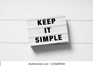 keep it simple text on lightbox sign, minimal flat lay design on white wooden background, simplicity or minimalism concept