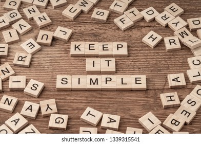 Keep it simple written with cube letters on wooden background