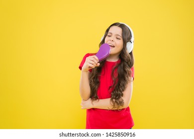 Keep a song in your heart. Adorable song singer. Cute small child doing vocal on song on yellow background. Little girl singing song playing in headphones.