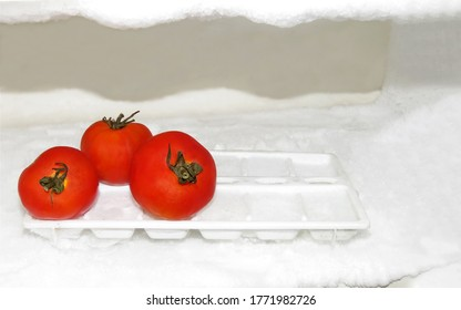 Keep Vegetables Fresh Concepts,Red tomatoes on the Ice cubes inside Refrigerator,keep vegetable freshness longtime.Food preservatives concept.Fresh Tomatoes on ice background.