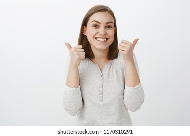 Keep up you doing great. Portrait of charming friendly-looking woman cheering from friend supporting him on competition raising thumbs up in cheer and like standing pleased, approving cool idea