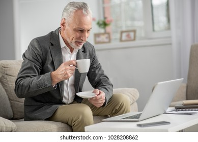 Keep your attention. Attractive businessman holding cup in right hand and keeping smile on his face while looking at computer