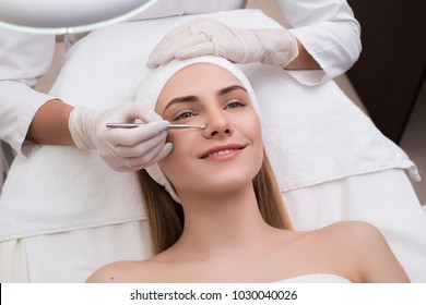 Keep your beauty! Beautiful woman getting skin cleaning and face treatment at beauty salon cosmetologist takes care of her face.