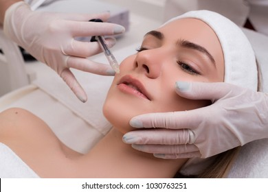 Keep your beauty! Young woman lying with pleasure gets beauty facial injections in the cosmetology salon.