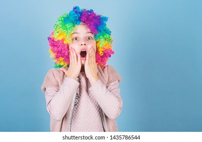 Keep your eyes for a surprise. Cute small girl opened mouth with big surprise. Surprised little girl wearing clown hair wig. Adorable little kid with surprise face. Looking with surprise, copy space.