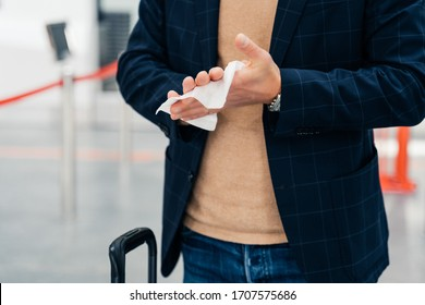 Keep your hands clean. Cropped shot of unrecognizable man disinfects hands with antibacterial napkin or antiseptic wet wipe during coronavirus spread, prevents virus, wants to be safe poses in airport