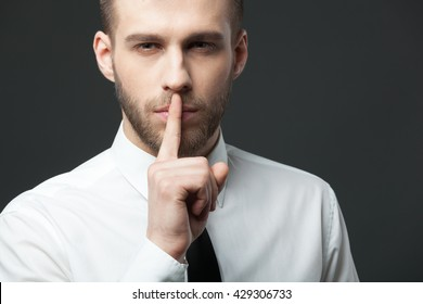"Keep your secrets! Studio portrait of young handsome businessman gesturing ""shh"" to the camera."