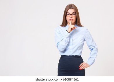"""Keep your secrets! Studio portrait of young beautiful business woman gesturing """"shh"""" to the camera."""