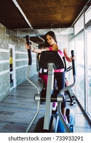 Keep yourself fit. Delighted young pretty girl training on a treadmill and smiling while having her workout in a gym