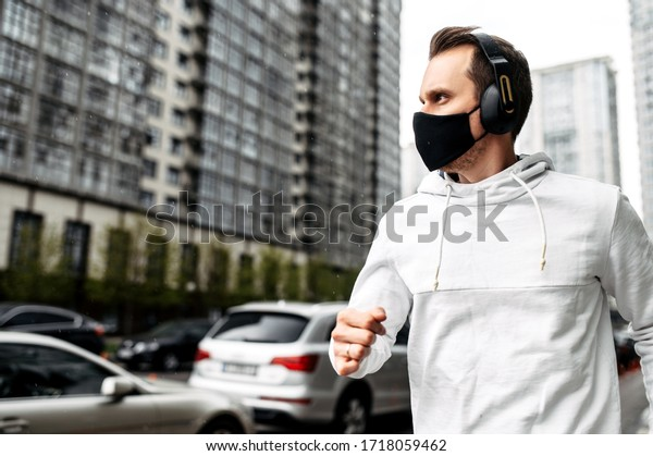 Keep yourself in shape during quarantine. Athletic young man is jogging in a protective mask among high-rise buildings. Healthy lifestyle concept