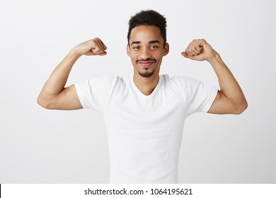 Keeping body fit and healthy. Portrait of satisfied confident african man with afro haircut raising hands, showing muscles, smiling broadly, bragging about his achievements in gym over gray wall