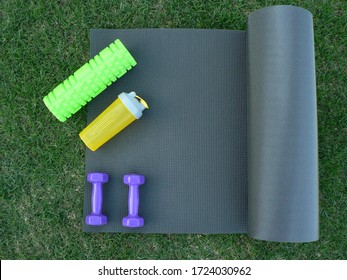 Keeping fit and exercising outdoor or at home. Purple dumbbells, yellow bottle for water, green foam roll on a yoga mat on green grass lawn in a backyard or park. Healthy lifestyle. Copy space.