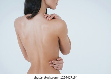 Keeping hands on the body. Young brunette girl turn her back to the camera while staying naked on the white background.