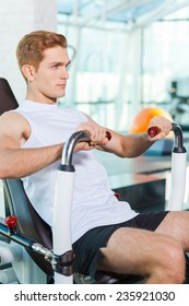 Keeping his body in perfect form. Concentrated young man working out in gym