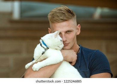 Keeping his cat happy. Muscular man hold cute pedigree cat. Happy cat owner with muscular look. Happy man on walk with pet. Cat relaxes in arms of his owner.