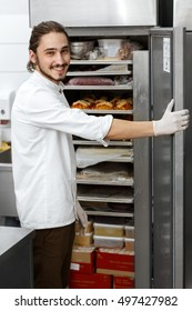 Keeping ingredients fresh and cool. Cheerful handsome male chef smiling to the camera over his shoulder while opening a refrigerator at his kitchen