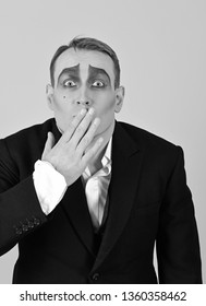 Keeping secret. Mime artist cover mouth with hand. Mime with face paint. Man actor with mime makeup. Theatre actor miming. Theatrical performance art and pantomime. Comedian or tragedian performer.