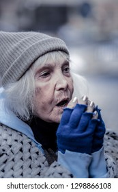 Keeping warm. Depressed aged woman breathing at her hands while trying to keep warm