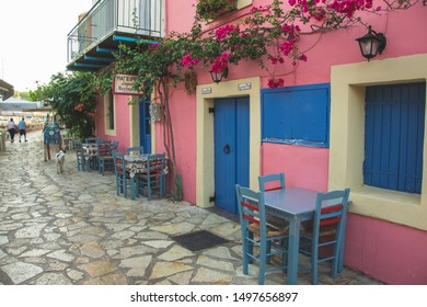 Kefalonia, Greece - 1 September 2019: Lovely small street with blue and pink house in Fiscardo. One of the coolest neighberhood in Kefalonia.