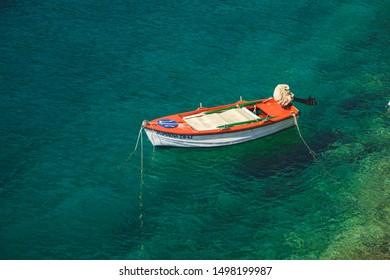 Kefalonia, Greece - 1 September 2019: Small boat in Fiscardo, Foki Beach. Orange/white boat on the green water.