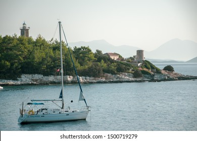 Kefalonia, Greece - 1 September 2019: View to Venetian lighthouse in Fiscardo with sailing boats