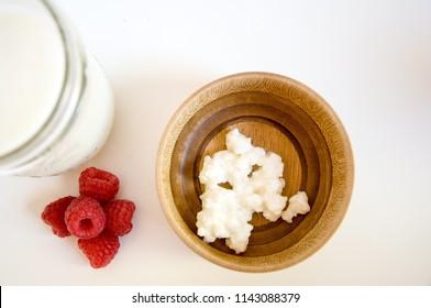 Kefir grains in bamboo wood bowl with organic raspberries and kefir in jar