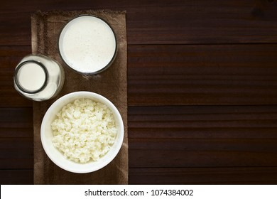 Kefir grains in bowl, fresh kefir drink in glass and a bottle of milk, photographed overhead with natural light (Selective Focus, Focus on the kefir grains and the kefir drink)