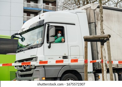 Kehl, Germany - Mar 16, 2020: Truck driver in Mercedes-Benz Actros wearing a protection mask shows OK sign during the border crossing Strasbourg Kehl crisis measures against the novel coronavirus