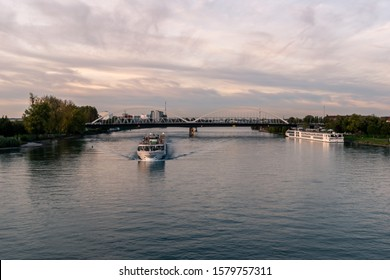 Kehl, Germany - October 26, 2019: In front is Voyager Cruise Ship sailling over the Rhine river. On the right, Viking Cruise Ship is anchored to the shore, tourists visiting the city of Kehl.