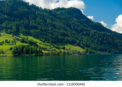 Kehrsiten, Nidwalden / Switzerland - June 9 2018: Village of Kehrsiten on the banks of Lake Lucerne with alpine pastures in the background