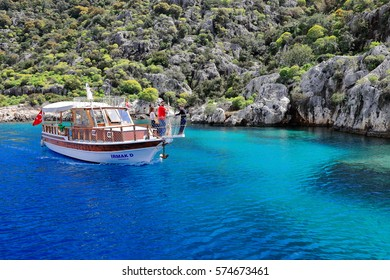 Kekova island, Turkey-April 2, 2015: Tourist boat sails over the partly sunken ruins of Dolichiste ancient Lycian town along the northern shore of Kekova island facing Kaleköy village-ancient Simena.