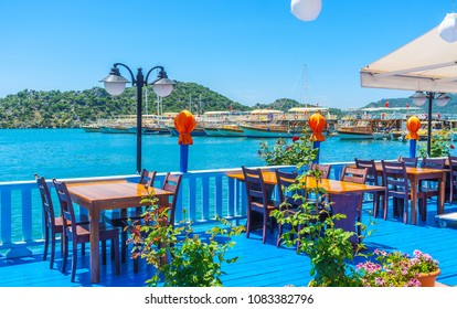 KEKOVA, TURKEY - MAY 10, 2017: The bright blue wooden terrace of outdoor cafe with a view on yachts and boats in harbor of Ucagiz, Kekova, Turkey.