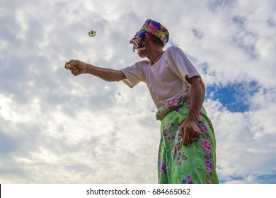 "KELANTAN, MALAYSIA - 15TH JULY 2017; Unidentified man is playing the traditional moon kite or locally known as ""Wau Bulan"" in Kelantan, Malaysia."