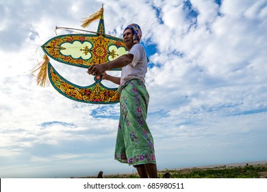 "KELANTAN, MALAYSIA - 15TH JULY 2017; Unidentified man holding the traditional moon kite or locally known as ""Wau Bulan"" in Kelantan, Malaysia."