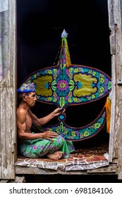 "KELANTAN, MALAYSIA - 15TH JULY 2017; Unidentified man is making the traditional moon kite or locally known as ""Wau Bulan"" at Kelantan, Malaysia."