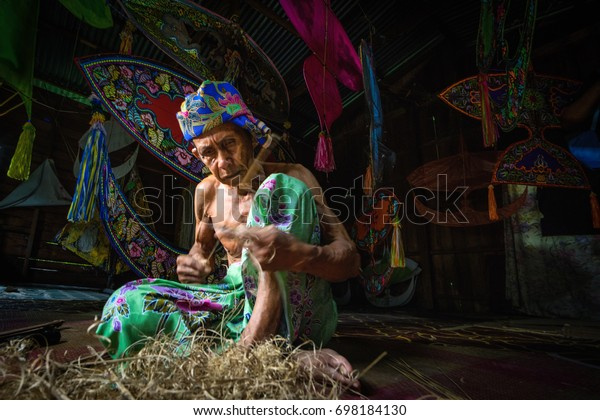 "KELANTAN, MALAYSIA - 15TH JULY 2017; Unidentified man is making the traditional moon kite or locally known as ""Wau Bulan"" at Kelantan, Malaysia."