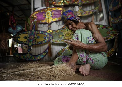 "KELANTAN, MALAYSIA - 16TH JULY 2017; Unidentified man is making the traditional moon kite or locally known as ""Wau Bulan"" at Kelantan, Malaysia."