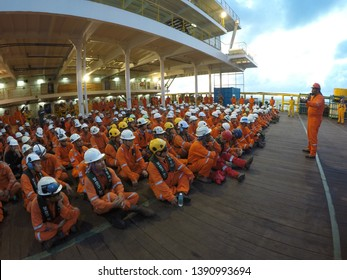 KELANTAN, MALAYSIA - JAN 05 2016 : Front view of Korean and local offshore workers together assemble on main deck listening safety talk by Safety Officer during toolbox meeting prior to start work.