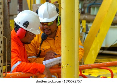 KELANTAN, MALAYSIA - MAY 05 2019 : Unidentified offshore contractor and client with full Personal Protective Equipment (PPE) having discussion during site visit at the oil and gas platform.