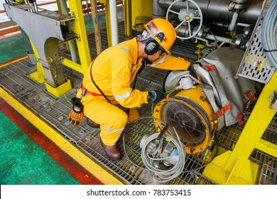KELANTAN, MALAYSIA - OCTOBER 10 2017 : Unidentified offshore worker complete with Personal Protective Equipment (PPE) doing inspection of industrial air blower condition prior to start work.