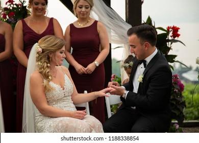 Kelowna, British Columbia / Canada - 08 10 2018:  Bride and groom exchanging rings